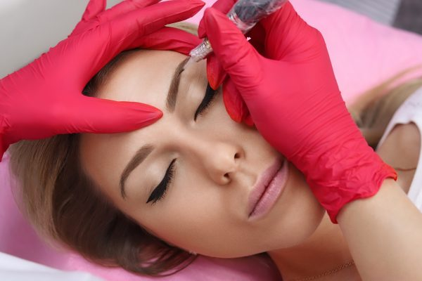 Healthy Spa: Young Beautiful Woman Having Permanent Make-up (Tattoo) on her brow. Close-up